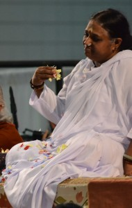 "Amma tossing flower petals during the ""Waving of the Light."" From TheBhaktiBeat.com"